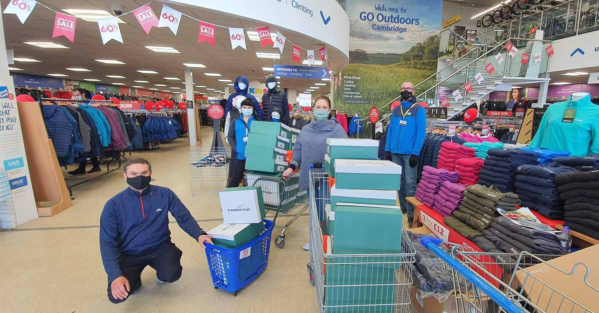 Kal Karim (left) and Melody Brooker (centre) collect the order of footwear from Go Outdoors, Cambridge
